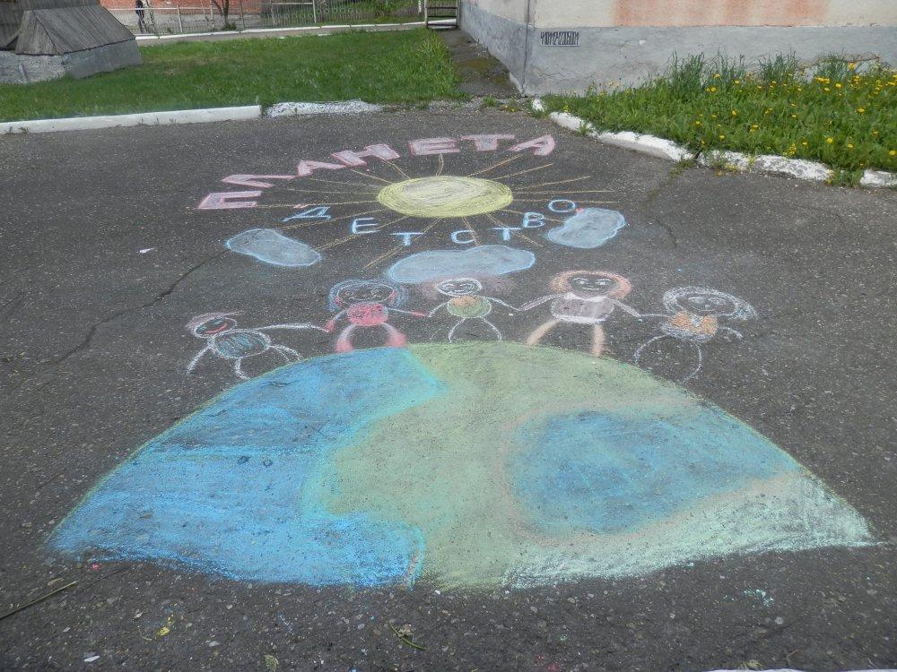 Рисует картинки на асфальте